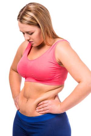 donne obese: La donna grassa infelice con il suo corpo isolato su sfondo bianco Archivio Fotografico