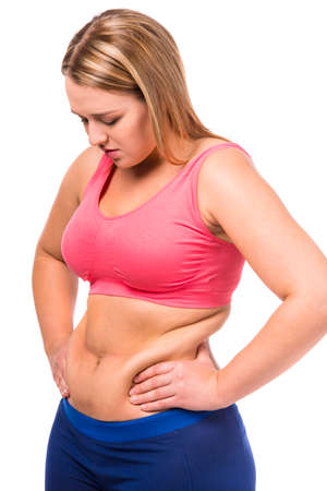 sobrepeso: La mujer gorda infeliz con su cuerpo aislado en fondo blanco Foto de archivo