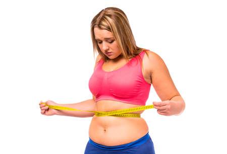 Fette Frau mit ihrem Körper, die Ernährung unglücklich, misst der Körper den isolierten weißen Hintergrund