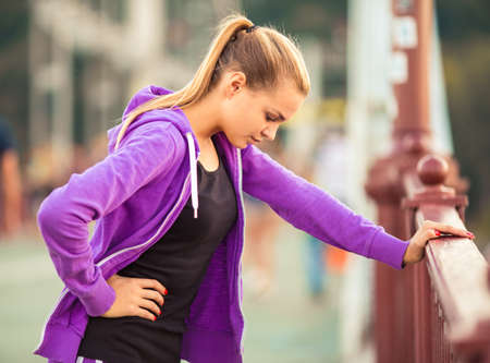 girl woman: The young beautiful girl with headphones running and doing fitness in city