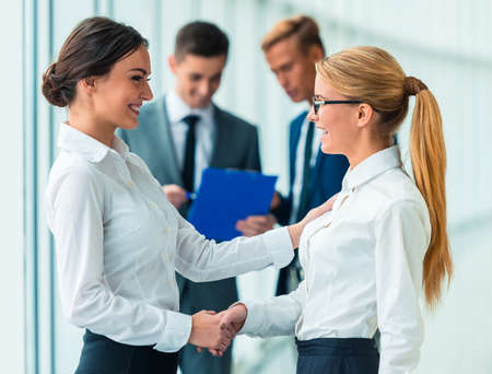 corporate women: Handshake two business women on the background of their colleagues in the office