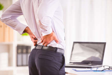 lower back pain: Disease back. Portrait of a businessman with a beard while working in his office, holding behind his back Stock Photo