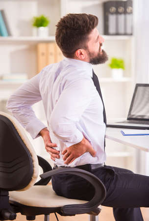 low back: Disease back. Portrait of a businessman with a beard while working in his office, holding behind his back Stock Photo