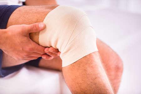 piernas hombre: Retrato de un hombre joven con la pierna lesionada en el hogar