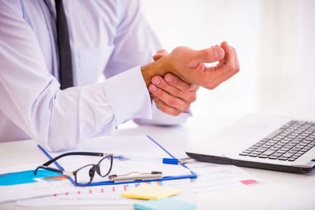 Krankheit Hand. Portrait eines Geschäftsmannes mit einem Bart während der Arbeit in seinem Büro, Hand halten