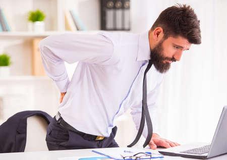 epaule douleur: Retour de la maladie. Portrait d'un homme d'affaires avec une barbe tout en travaillant dans son bureau, tenant derri�re son dos