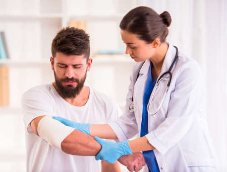 doctor care: Injury hands. Young man with injured hands. Young woman doctor helps the patient
