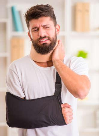 pierna rota: Retrato de un hombre joven con el cuello y la mano lesionada en el hogar Foto de archivo