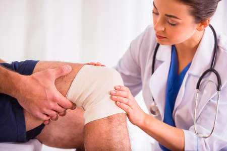 broken foot: Injury leg. Young man with injured leg. Young woman doctor helps the patient Stock Photo