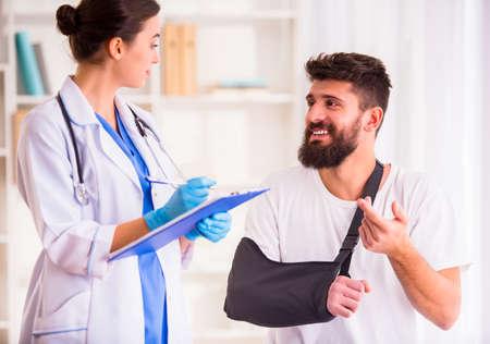 zbraně: Zranění ruce. Mladý muž s rukama zraněných. Mladá žena lékař pomáhá pacientovi Reklamní fotografie