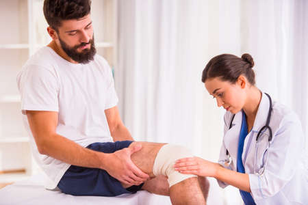 adult foot: Injury leg. Young man with injured leg. Young woman doctor helps the patient Stock Photo