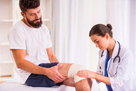 fractura: Lesiones pierna. Hombre joven con la pierna lesionada. Mujer Joven médico ayuda al paciente