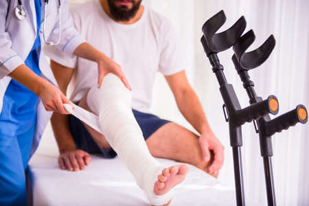 plaster: Injury leg. Young man with injured leg. Young woman doctor helps the patient Stock Photo