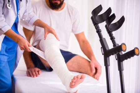 piernas hombre: Lesiones pierna. Hombre joven con la pierna lesionada. Mujer Joven médico ayuda al paciente