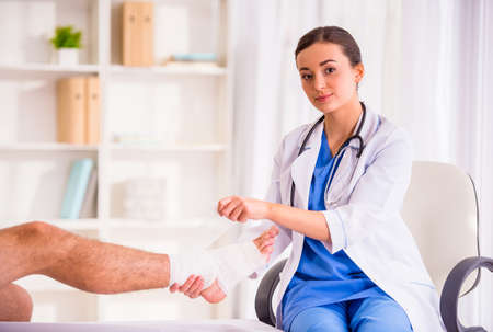 plaster leg cast: Injury leg. Young man with injured leg. Young woman doctor helps the patient Stock Photo