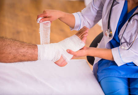hospital: Injury leg. Young man with injured leg. Young woman doctor helps the patient Stock Photo