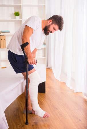 家庭でけがをした脚を持つ若者の肖像