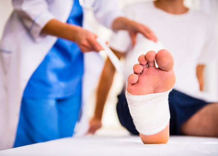 Injury leg. Young man with injured leg. Young woman doctor helps the patient Stock Photo