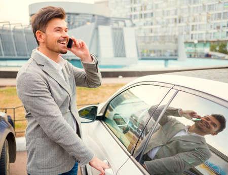 Portret van een jonge succesvolle zakenman in de voorkant van zijn auto op een achtergrond van office center Stockfoto