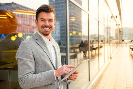 Portrét mladého úspěšného obchodníka na pozadí kancelářské centrum
