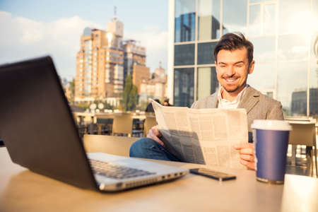 hombres guapos: El joven exitoso hombre de negocios, sentado en una mesa en su oficina usando la computadora port�til Foto de archivo