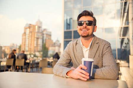 사무실 중앙에 젊은 성공적인 사업가 커피를 마시는
