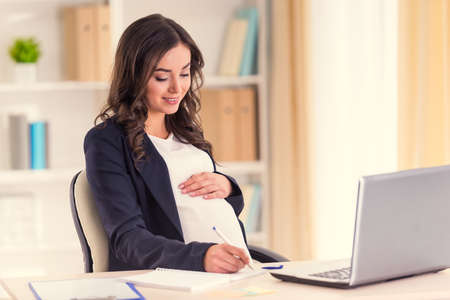 Junge schwangere Frau mit einem Business-Laptop im Büro mit Lizenzfreie Bilder