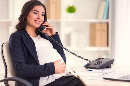 Glückliche schwangere Frau am Telefon zu sprechen, während der Arbeit im Büro
