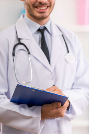 a white robe: Young doctor with a stethoscope in a white robe holding a card. Close-up Stock Photo