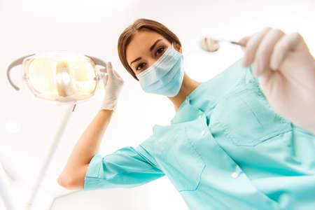 Jonge vrouwentandarts in beschermingshandschoenen en een masker, houdt tandheelkundig instrument bekijkend de camera.