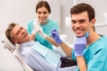 Jonge tandarts en zijn assistent behandeling van oudere man