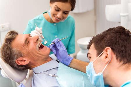 Mladý zubař a jeho asistent léčbě starší muž
