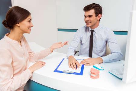Vrouwelijke patiënt met arts het invullen en ondertekenen van formulieren
