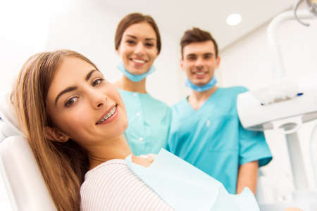 dental office: Close-up of a young attractive girl with braces on the teeth, at a reception at the dentist in the background dentist and assistant