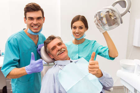 Young doctor dentist and his assistant, elderly patient showing thumb up, smiling and looking at the camera Imagens