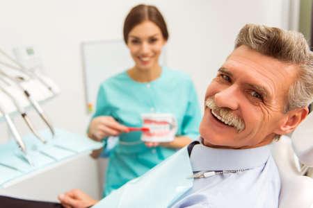 odontologa: El hombre mayor en una revisión de un dentista, sentado en una silla