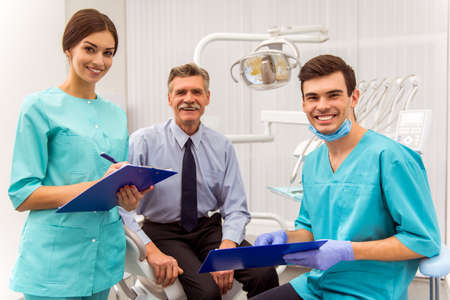 Young doctor dentist and his assistant recording in the documents. An elderly man sitting in the dental chair