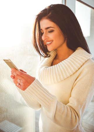 Mooi meisje om thuis te zitten bij een raam met een glimlach kijken naar telefoon