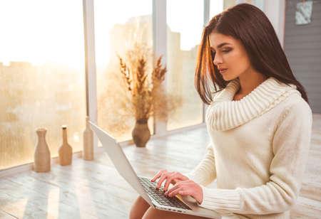 Hermosa niña sentada en el piso en casa trabajando en un ordenador portátil Foto de archivo