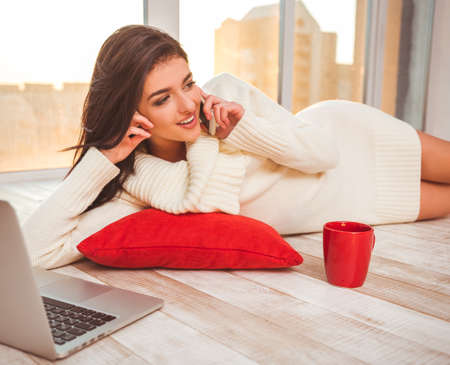 Hermosa joven tendido en un colchón rojo en el suelo y hablando por teléfono. Cerca se encuentran un ordenador portátil y una taza
