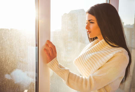 Beautiful young woman looking out the window at home Imagens