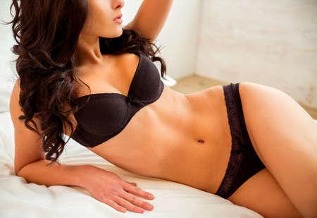 Belle jeune fille en lingerie noire posant sur le lit à la maison Banque d'images