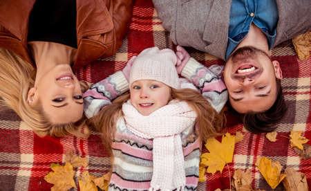 mom and dad: Happy young family lying on the blanket while walking in the autumn park. Top review Stock Photo