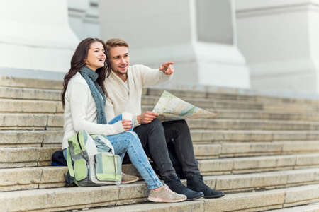 Young happy couple traveling with maps in hand in the city Stock Photo