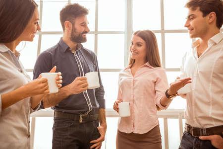 amigas conversando: Café chat durante la pausa. Grupo de hombres de negocios atractivos, de pie junto a la otra, lleva a cabo un tazas, sonriendo de pie junto a la ventana