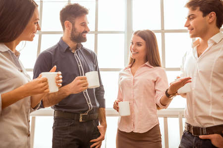 break: Coffee break chat. Group of attractive business people, standing next to each other, holding a cups, smiling standing at the window