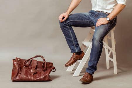 Młody człowiek biznesu z brązowym skórzanym worku, białą koszulę i niebieskie dżinsy na szarym tle