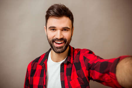 Beautiful young man with a beard in checkered shirt makes self, smiling, on a gray background Stock Photo