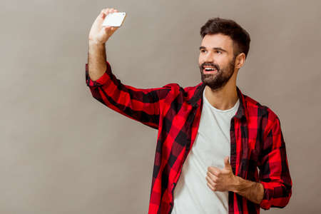 narcissist: Beautiful young man with a beard in checkered shirt makes self, smiling, on a gray background Stock Photo