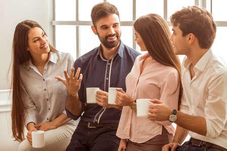 Café chat durante la pausa. Grupo de hombres de negocios atractivos, de pie junto a la otra, lleva a cabo un tazas, sonriendo de pie junto a la ventana